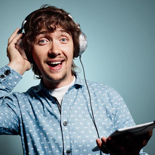 Junger Mann mit Kopfhörer am Musik hören.