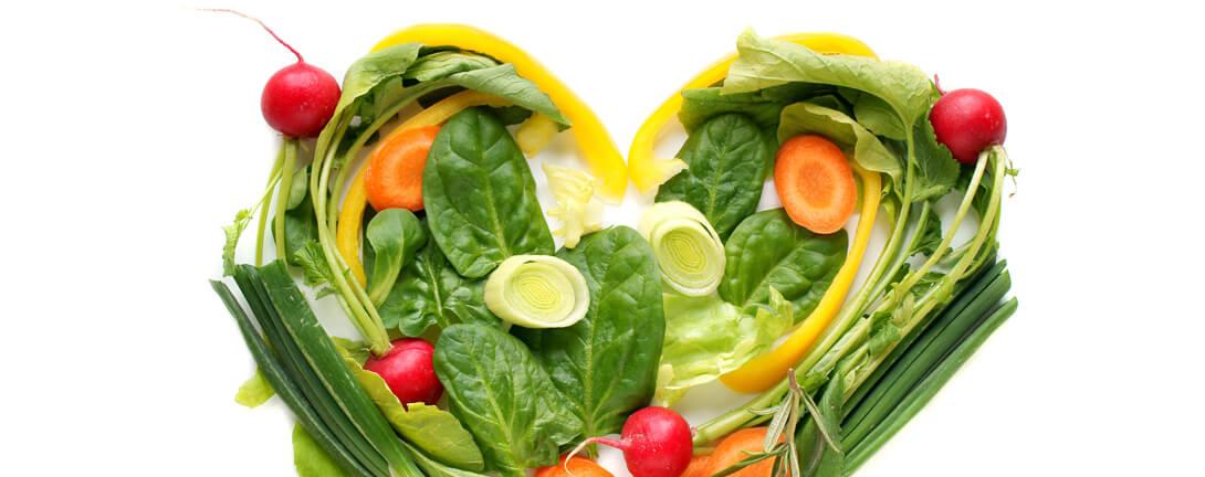Ein Herz geformt aus verschiedenem Gemüse. Salat, Karotten, Tomaten, Peperoni.