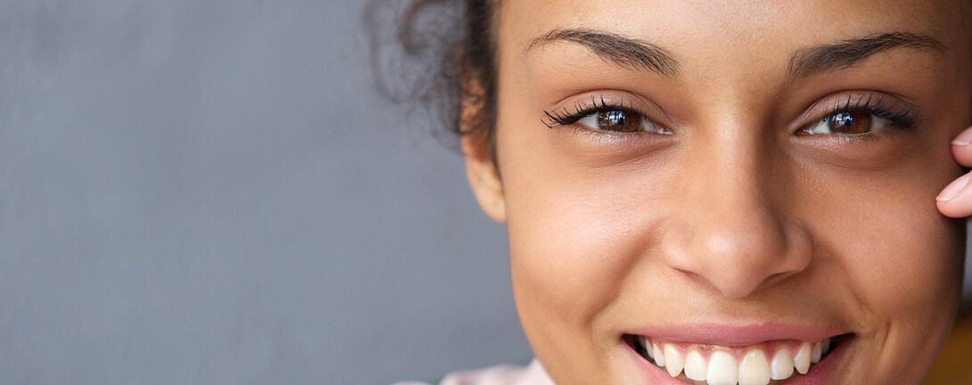 Junge Lachende südländische Frau mit Schwarzen Locken und braunen Augen.
