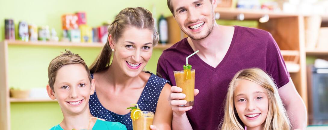 Fröhliche Familie mit zwei Kinder trinken zusammen einen Smoothie/Gemüsesaft.