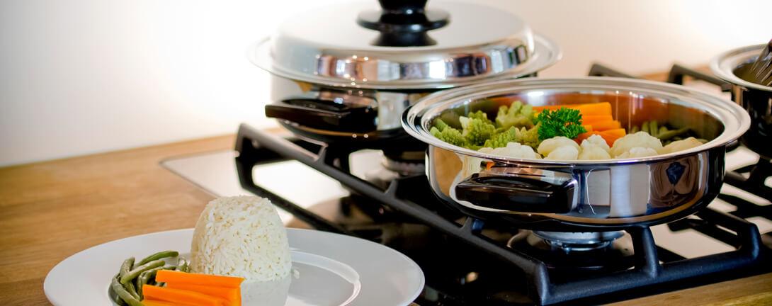 Drei Pfannen auf Herdplatten mit Gemüse. Angerichtetes Teller mit Reis, Bohnen und Karotten.