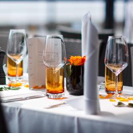 Gedeckter Tisch mit Blumen, Serviette, Weingläser und einer Speisekarte.