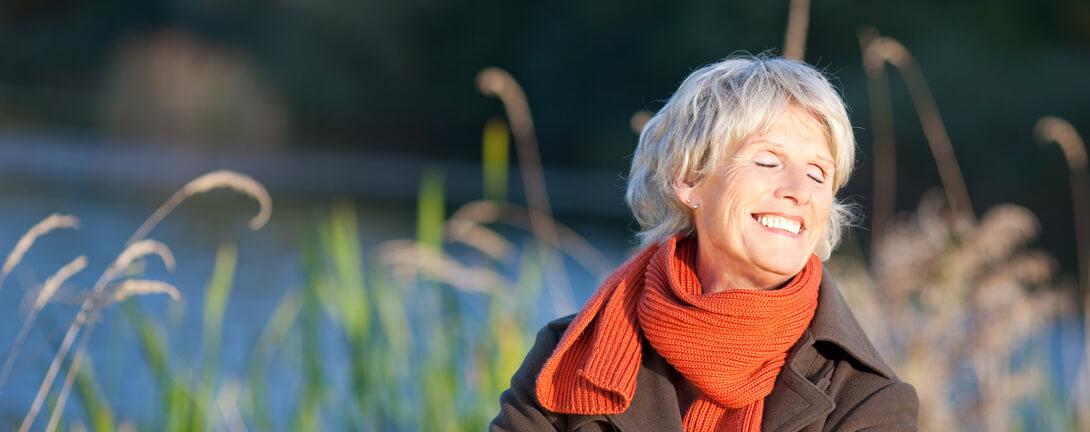 Glückliche ältere Frau in der Abendsonne mit schwarzer Jacke und orange farbenen Schal.