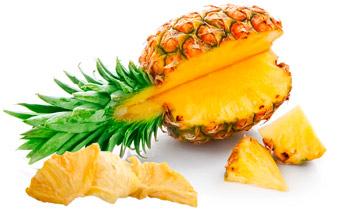 Frisch aufgeschnittene Ananas, daneben getrocknete Ananasschnitze.