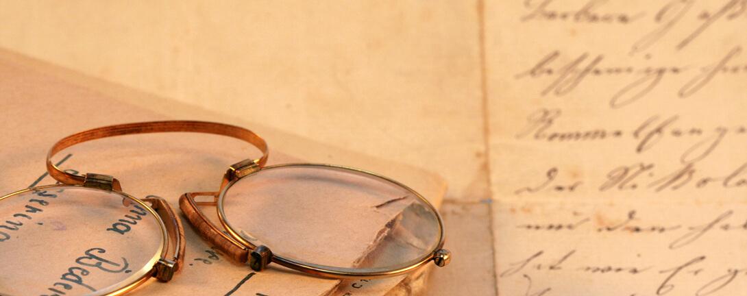 Uralte Brille auf einem altem Buch. Im Buch wurde mit alter Schrift geschrieben.