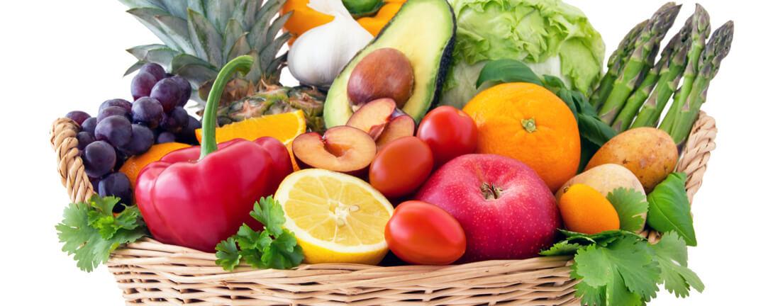 Gemüse- und Früchtekorb mit Avocado, Äpfeln, Orangen, Tomaten, Aprikosen, Zitrone.
