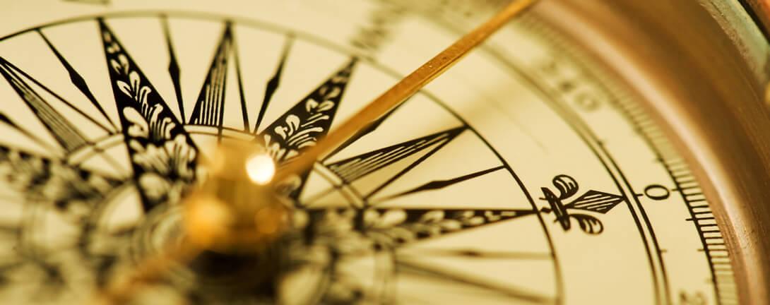 Antiker Kompass mit goldener Nadel und schwarzer Beschriftung.