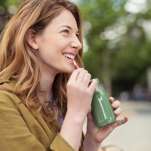 Junge Frau trinkt lachend einen Gemüsesmoothie mit einem Strohhalm.